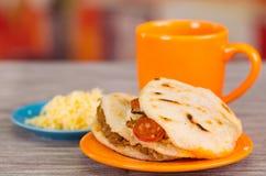 Παραδοσιακά εύγευστα arepas, τεμαχισμένο τυρί αβοκάντο κοτόπουλου και τυριού Cheddar και τεμαχισμένο βόειο κρέας με ένα πορτοκαλί Στοκ Εικόνες