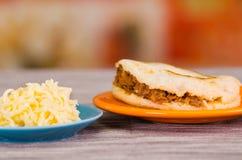 Παραδοσιακά εύγευστα arepas, τεμαχισμένο τυρί αβοκάντο κοτόπουλου και τυριού Cheddar και τεμαχισμένο βόειο κρέας στο ξύλινο black Στοκ Εικόνα