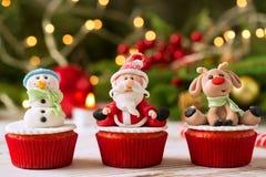 Παραδοσιακά διακοσμημένα Χριστούγεννα τρία cupcakes με την πλάτη festice στοκ εικόνα με δικαίωμα ελεύθερης χρήσης