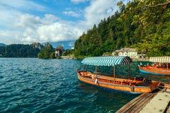 Παραδοσιακές ξύλινες βάρκες Pletna στη λίμνη που αιμορραγείται Στοκ Φωτογραφίες