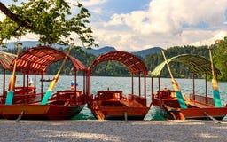 Παραδοσιακές ξύλινες βάρκες Pletna στη λίμνη που αιμορραγείται Στοκ Φωτογραφία
