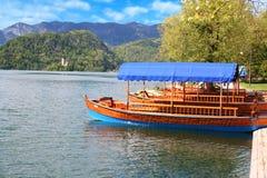 Παραδοσιακές ξύλινες βάρκες Pletna στη λίμνη που αιμορραγείται Στοκ Εικόνες