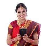 Παραδοσιακή γυναίκα που κρατά το κινητό τηλέφωνο και που ενάντια στο λευκό στοκ φωτογραφία με δικαίωμα ελεύθερης χρήσης