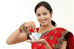 Παραδοσιακή ινδική γυναίκα που κρατά μια piggy τράπεζα Στοκ εικόνα με δικαίωμα ελεύθερης χρήσης