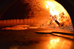 Παραδοσιακή ιταλική πίτσα που ψήνεται στο φούρνο ξύλινος-πυρκαγιάς Στοκ Φωτογραφία
