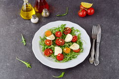 Παραδοσιακή ιταλική σαλάτα με την ντομάτα κερασιών, ruccola, μοτσαρέλα, ξίδι κρασιού ελαιολάδου σε ένα άσπρο πιάτο σε ένα γκρι Στοκ φωτογραφία με δικαίωμα ελεύθερης χρήσης