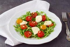 Παραδοσιακή ιταλική σαλάτα με την ντομάτα κερασιών, ruccola, μοτσαρέλα, ξίδι κρασιού ελαιολάδου σε ένα άσπρο πιάτο σε ένα γκρι Στοκ Εικόνα