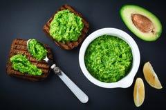 Παραδοσιακή μεξικάνικη σάλτσα guacamole στο κεραμικό άσπρο μισό αβοκάντο κύπελλων, λεμονιών και περικοπών στο σκοτεινό υπόβαθρο Στοκ εικόνες με δικαίωμα ελεύθερης χρήσης