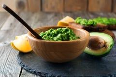Παραδοσιακή μεξικάνικη σάλτσα guacamole στο κύπελλο μπαμπού, το λεμόνι και το μισό αβοκάντο περικοπών στο παλαιό ξύλινο υπόβαθρο Στοκ φωτογραφία με δικαίωμα ελεύθερης χρήσης