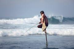 Παραδοσιακή Σρι Λάνκα: ξυλοπόδαρο που αλιεύει στην ωκεάνια κυματωγή Στοκ Φωτογραφίες