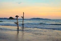 Παραδοσιακοί πόλοι Sri Lankan για την αλιεία Ένας από τους έχει ένα καπέλο Παραλία του ωκεανού στο ηλιοβασίλεμα Στοκ φωτογραφίες με δικαίωμα ελεύθερης χρήσης