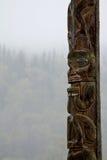 Παραδοσιακός πόλος τοτέμ Gitxsan με καλυμμένο το υδρονέφωση δάσος πίσω Στοκ Φωτογραφία