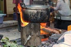 Παραδοσιακός της κατασκευής των τροφίμων με τα δοχεία στη σόμπα πέρα από έναν φυσικό Στοκ φωτογραφία με δικαίωμα ελεύθερης χρήσης
