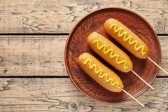 Παραδοσιακό αμερικανικό τηγανισμένο άχρηστο φαγητό πρόχειρο φαγητό λουκάνικων κρέατος χοτ ντογκ σκυλιών καλαμποκιού με τη μουστάρ Στοκ Φωτογραφίες