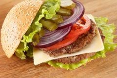 Παραδοσιακό αμερικανικό cheeseburger Το κρέας, το κουλούρι και τα λαχανικά κλείνουν επάνω στοκ εικόνες με δικαίωμα ελεύθερης χρήσης