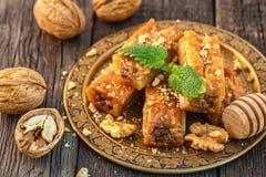 Παραδοσιακό αραβικό επιδόρπιο Baklava με το μέλι και τα ξύλα καρυδιάς Στοκ Φωτογραφίες