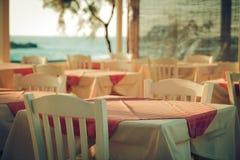 Παραδοσιακό ελληνικό υπαίθριο εστιατόριο στο πεζούλι που αγνοεί τη Μεσόγειο Ελλάδα κενός πίνακας σε μια θάλασσα οδών Στοκ Φωτογραφίες