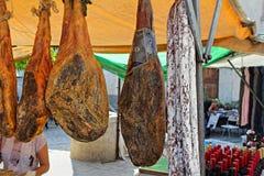 Παραδοσιακό ισπανικό ζαμπόν ποδιών και κόκκινο κρασί στην αγορά τροφίμων Στοκ Φωτογραφία