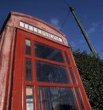 Παραδοσιακό κόκκινο τηλεφωνικό περίπτερο με τον πόλο τηλέγραφων στο υπόβαθρο Στοκ εικόνα με δικαίωμα ελεύθερης χρήσης