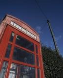 Παραδοσιακό κόκκινο τηλεφωνικό περίπτερο με τον πόλο τηλέγραφων στο υπόβαθρο Στοκ φωτογραφία με δικαίωμα ελεύθερης χρήσης