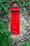 Παραδοσιακό παλαιό αγγλικό κόκκινο ταχυδρομικό κουτί που τοποθετείται στον τοίχο πετρών που περιβάλλεται από τον κισσό Στοκ Φωτογραφία
