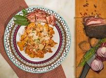 Παραδοσιακό πιάτο με το σπιτικό all'amatriciana tortellini, που διακοσμείται με ένα φύλλο κόλπων και ένα μπέϊκον Στοκ Φωτογραφία