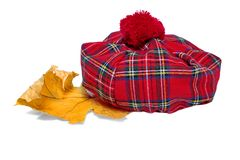 Παραδοσιακό σκωτσέζικο κόκκινο καπό ταρτάν και ξηρό φύλλο σφενδάμου στοκ φωτογραφίες