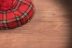 Παραδοσιακό σκωτσέζικο κόκκινο καπό ταρτάν στον ξύλινο πίνακα Στοκ Εικόνα