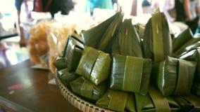 Παραδοσιακό ταϊλανδικό επιδόρπιο που τυλίγεται στα φύλλα μπανανών απόθεμα βίντεο