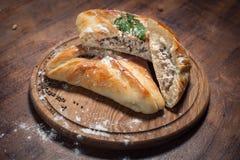 Παραδοσιακό της Γεωργίας ψημένο kubdari τροφίμων στον ξύλινο πίνακα  Στοκ Εικόνες