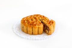 Παραδοσιακό mooncake με το μίγμα πέντε καρύδια που γεμίζουν doily εγγράφου Στοκ Φωτογραφίες