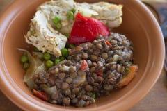 Παραδοσιακό stew κοτόπουλου και φακών σε ένα σπιτικό κεραμικό πιάτο Στοκ Φωτογραφία