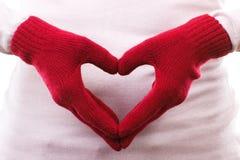 Παραδώστε τα μάλλινα γάντια που τακτοποιούνται στη μορφή της καρδιάς, σύμβολο της αγάπης Στοκ εικόνα με δικαίωμα ελεύθερης χρήσης