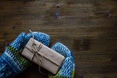 Παραδώστε τα πλεκτά γάντια κρατώντας το παρόν, αγροτικό ξύλινο υπόβαθρο στοκ φωτογραφία με δικαίωμα ελεύθερης χρήσης