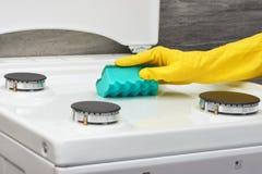 Παραδώστε το κίτρινο γάντι που καθαρίζει την άσπρη σόμπα με το πράσινο σφουγγάρι Στοκ εικόνες με δικαίωμα ελεύθερης χρήσης