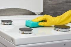 Παραδώστε το κίτρινο γάντι που καθαρίζει την άσπρη σόμπα με το πράσινο σφουγγάρι Στοκ φωτογραφία με δικαίωμα ελεύθερης χρήσης