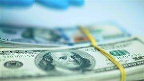 Παραδώστε το μπλε γάντι βάζει τις δέσμες των δεσμών αμερικανικών δολαρίων στην άσπρη επιφάνεια closeup φιλμ μικρού μήκους