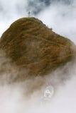 Παρεκκλησι και σταυρός βουνών στα σύννεφα Στοκ Εικόνες