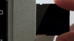 Παρεμβάλλει την κάρτα SD στο lap-top απόθεμα βίντεο