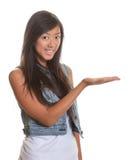 Παρουσίαση της ασιατικής γυναίκας σε ένα άσπρο υπόβαθρο στοκ εικόνες