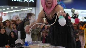 Παρουσιάστε για τους ανθρώπους στο εμπορικό κέντρο, το κορίτσι με τη ρόδινη περούκα κάνει τις φυσαλίδες σαπουνιών με το smok απόθεμα βίντεο