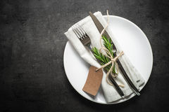 Παρουσιάστε την τιμή τών παραμέτρων Μαχαίρι δικράνων και άσπρο πιάτο στο σκοτεινό πίνακα πλακών Στοκ φωτογραφία με δικαίωμα ελεύθερης χρήσης