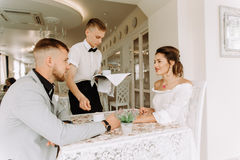 Παρουσιασμένο σερβιτόρος φλιτζάνι του καφέ για το όμορφο ζεύγος σε έναν καφέ Στοκ Φωτογραφία