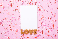 Παρούσα κάρτα με την αγάπη μπισκότων επιστολών και ροζ, κόκκινες καρδιές στο ρόδινο υπόβαθρο στοκ εικόνα με δικαίωμα ελεύθερης χρήσης