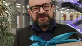 Παρόν κιβώτιο δώρων χαμόγελου επιχειρηματιών υπό εξέταση κλείστε επάνω απόθεμα βίντεο
