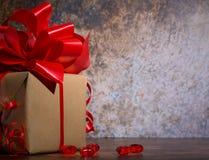 Παρόν κιβώτιο με την κόκκινη κορδέλλα τόξων και shinny μικρές καρδιές σε έναν ξύλινο αγροτικό πίνακα για την ημέρα βαλεντίνων στοκ εικόνες με δικαίωμα ελεύθερης χρήσης