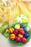 Παρόν Πάσχας με τα ζωηρόχρωμα αυγά Πάσχας στη φωλιά Πάσχας Στοκ εικόνα με δικαίωμα ελεύθερης χρήσης