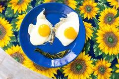 Παρόν πιάτο τροφίμων - το αστείο χαμόγελο προσώπων τροφίμων τηγάνισε το φυτικό στόμα ματιών αυγών στο μπλε ύφασμα ηλίανθων πιάτων Στοκ Εικόνες