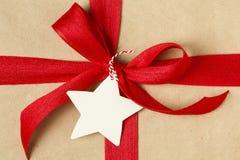 Παρόν δώρων Χριστουγέννων που διακοσμείται με το φωτεινό κόκκινο τόξο και την κενή ετικέττα δώρων Απλό, ανακυκλωμένο υπόβαθρο τυλ Στοκ εικόνα με δικαίωμα ελεύθερης χρήσης