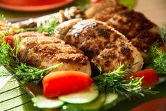 Πασπαλίζοντας με ψίχουλα cutlets κοτόπουλου σε ένα πιάτο με τις ντομάτες και το cucum άνηθου στοκ εικόνα